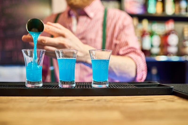 Barman Pouring Vodka Shots bij Barteller stock foto