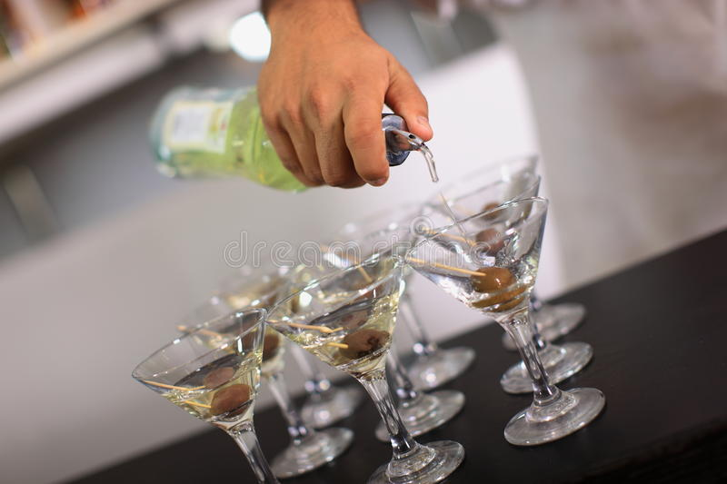 Barman pours martini stock photography