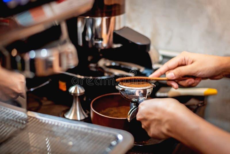 Barman préparant des grains de café grinded image stock