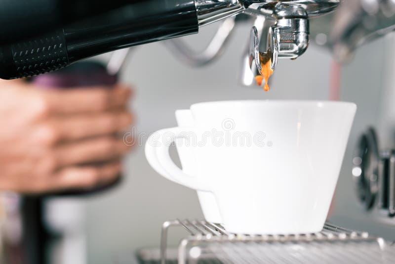 Barman préparant le café avec la machine de portafilter photographie stock