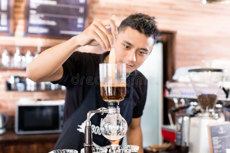 Barman préparant le café d'égouttement dans le café asiatique images stock