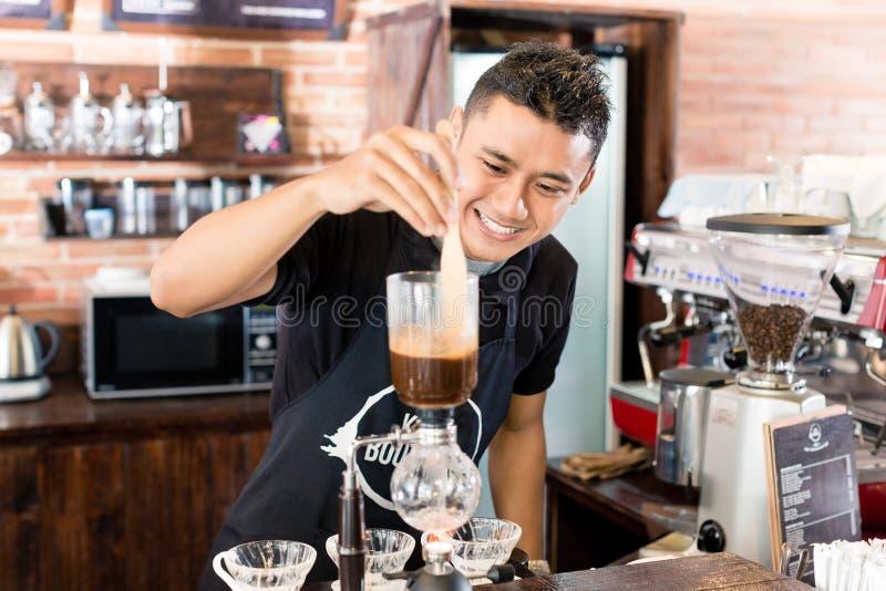 Barman préparant le café d'égouttement dans le café asiatique images libres de droits