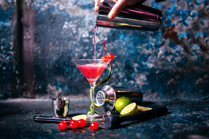 Barman preparing and pouring red cocktail in marini class. cosmopolitan cocktail on metal background. Barman preparing and pouring red cocktail in martini class royalty free stock photos