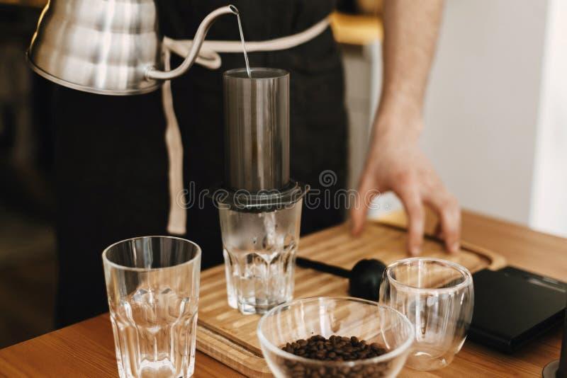 Barman professionnel dans le tablier élégant noir versant l'eau chaude dans les aeropress, méthode alternative de brassage de caf photos libres de droits
