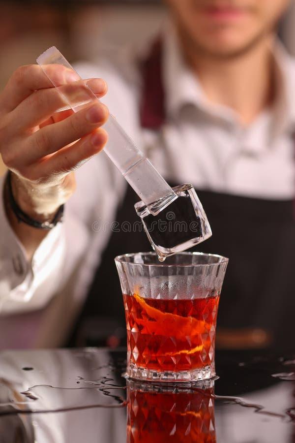 Barman professionnel jetant au verre de cocktail rouge photos stock