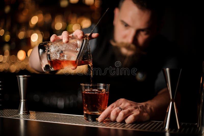 Barman professionnel versant un alcool de la tasse de mesure par le tamis au verre avec un grand glaçon photos libres de droits