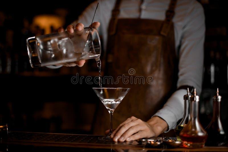 Barman profissional que derrama uma bebida alcoólica do copo de medição ao vidro de martini imagem de stock