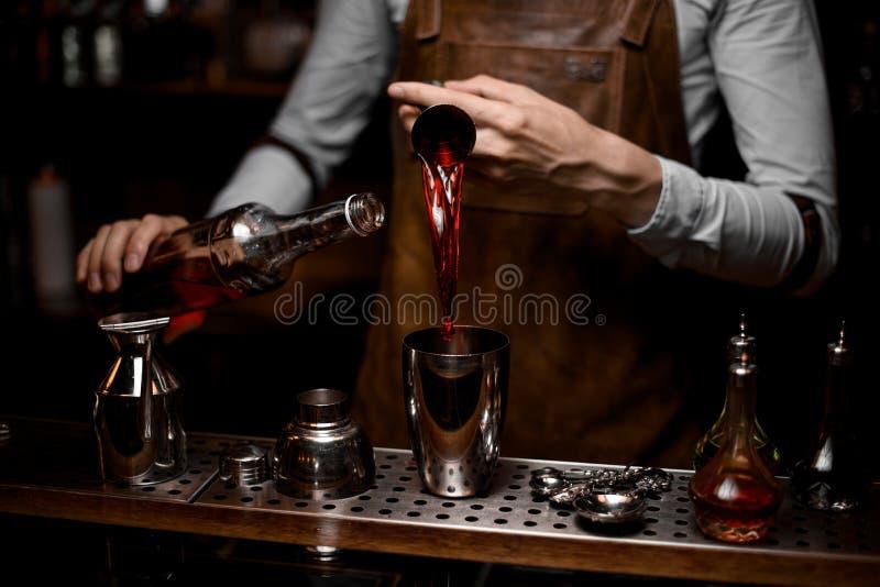 Barman profissional que derrama uma bebida alcoólica do jigger de aço ao abanador de cocktail imagens de stock