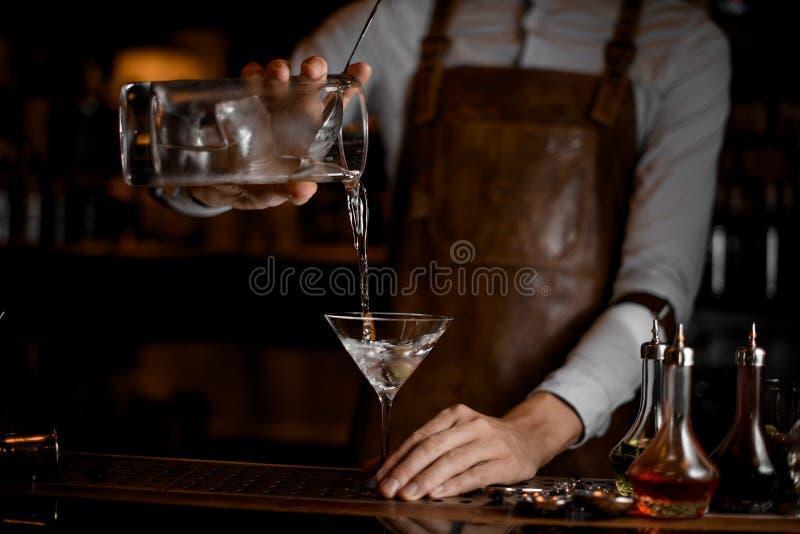 Barman profissional que derrama uma bebida alcoólica transparente do copo de medição ao vidro de martini imagem de stock royalty free