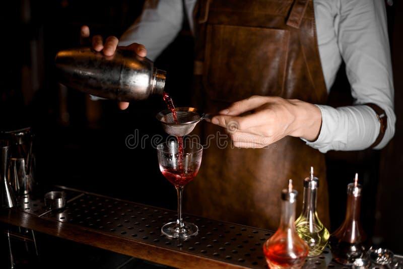 Barman profissional que derrama uma bebida alcoólica vermelha do abanador de aço através da peneira fotografia de stock royalty free