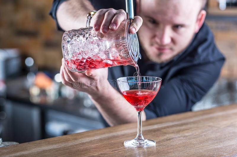 Barman in pub or restaurant preparing a cocktail drink stock photography