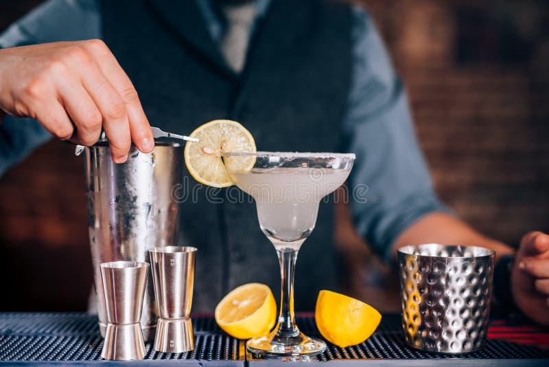 Barman que decora a bebida, margarita de derramamento do cal no vidro extravagante no restaurante foto de stock