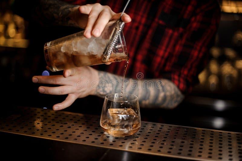 Barman que derrama a bebida fresca em um vidro do dof do uísque imagens de stock