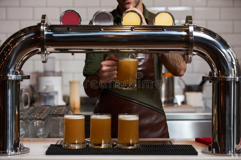 Barman que derrama a cerveja fresca no vidro de cerveja no contador da barra, close-up fotografia de stock