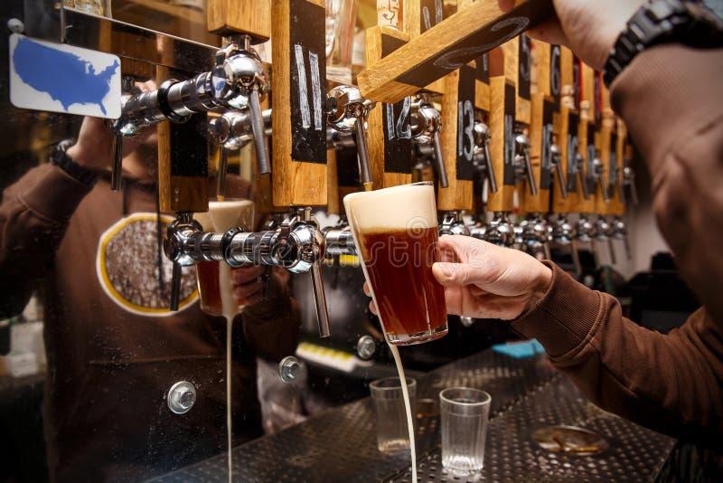 Barman que derrama da cerveja fresca da torneira no vidro no bar imagens de stock