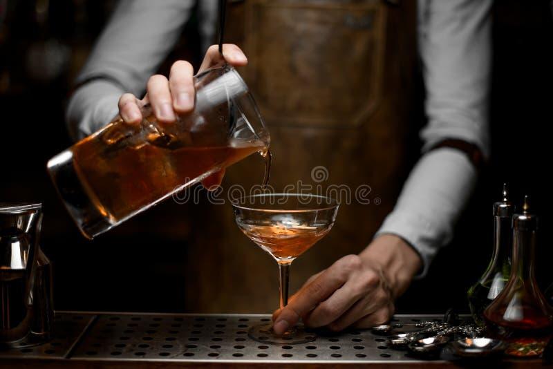 Barman que derrama um cocktail do álcool com filtro fotos de stock royalty free