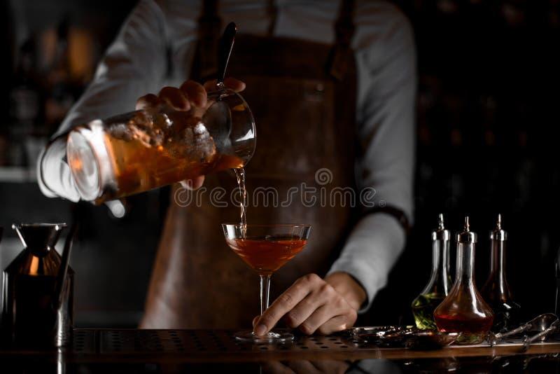 Barman que derrama um cocktail do álcool do filtro foto de stock royalty free
