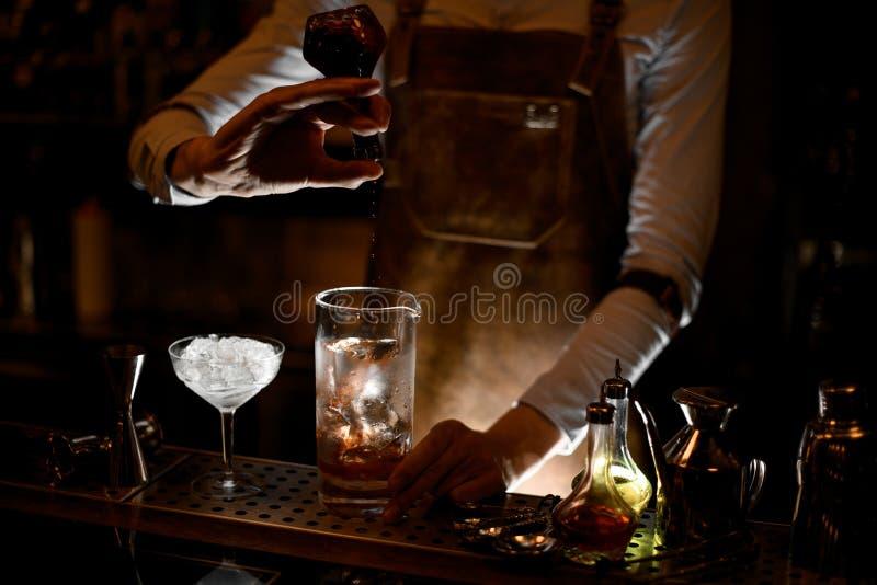 Barman que derrama um cocktail do tubo de ensaio no vidro fotos de stock