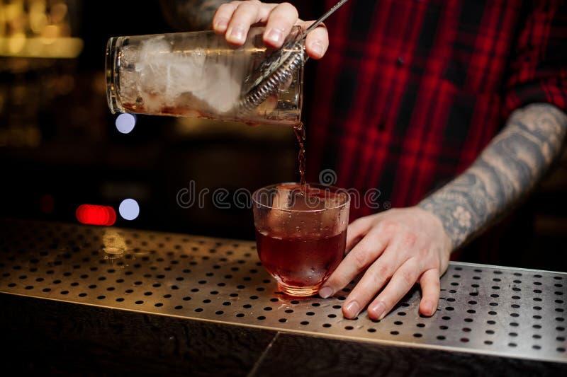 Barman que derrama um cocktail vermelho de Vieux Carre do copo de medição fotografia de stock royalty free