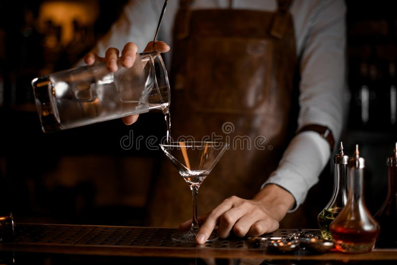 Barman que derrama uma bebida alcoólica do copo de medição ao vidro de martini imagem de stock royalty free