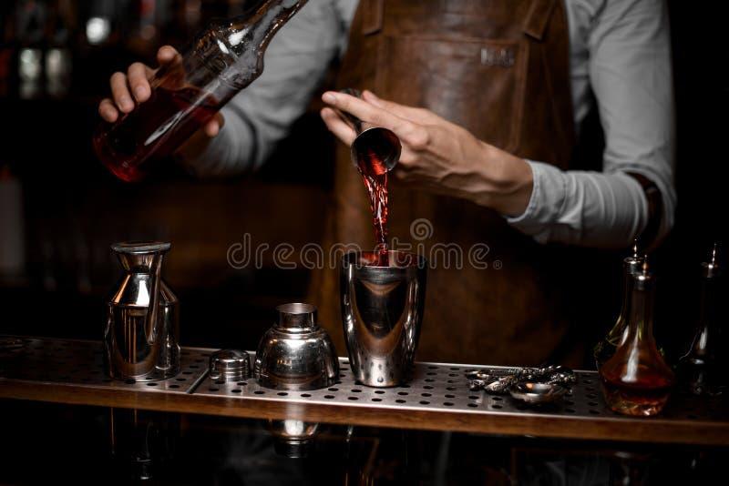 Barman que derrama uma bebida alcoólica do jigger de aço ao abanador de cocktail imagem de stock royalty free