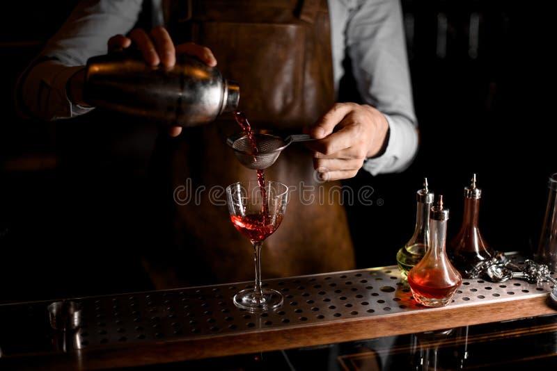 Barman que derrama uma bebida alcoólica vermelha do abanador de aço através da peneira imagem de stock