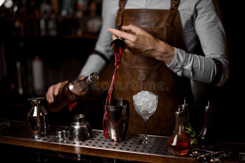 Barman que derrama uma bebida alcoólica vermelha do jigger de aço ao abanador de cocktail imagens de stock