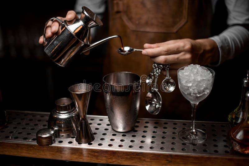 Barman que derrama uma essência da chaleira de aço à colher imagem de stock