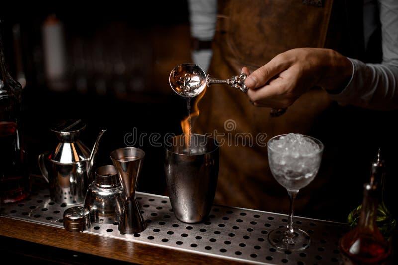 Barman que derrama uma essência da colher ao abanador de aço com fogo imagem de stock