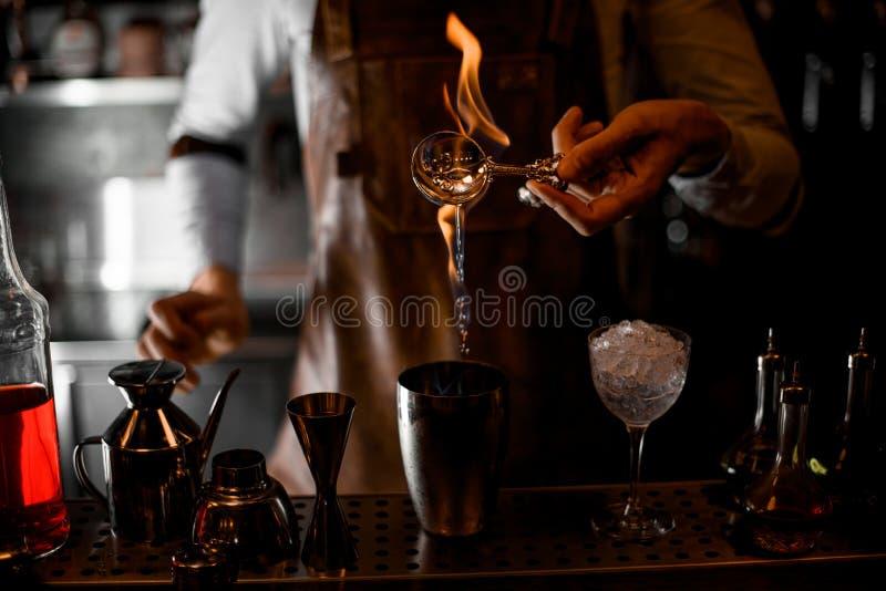 Barman que derrama uma essência da colher na chama ao abanador de aço fotos de stock royalty free