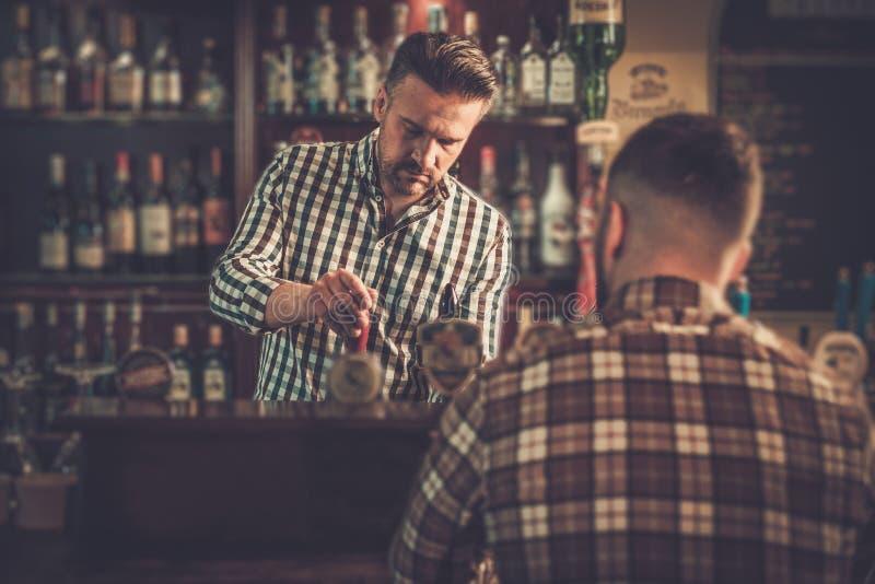Barman que derrama uma pinta da cerveja ao cliente em um bar foto de stock