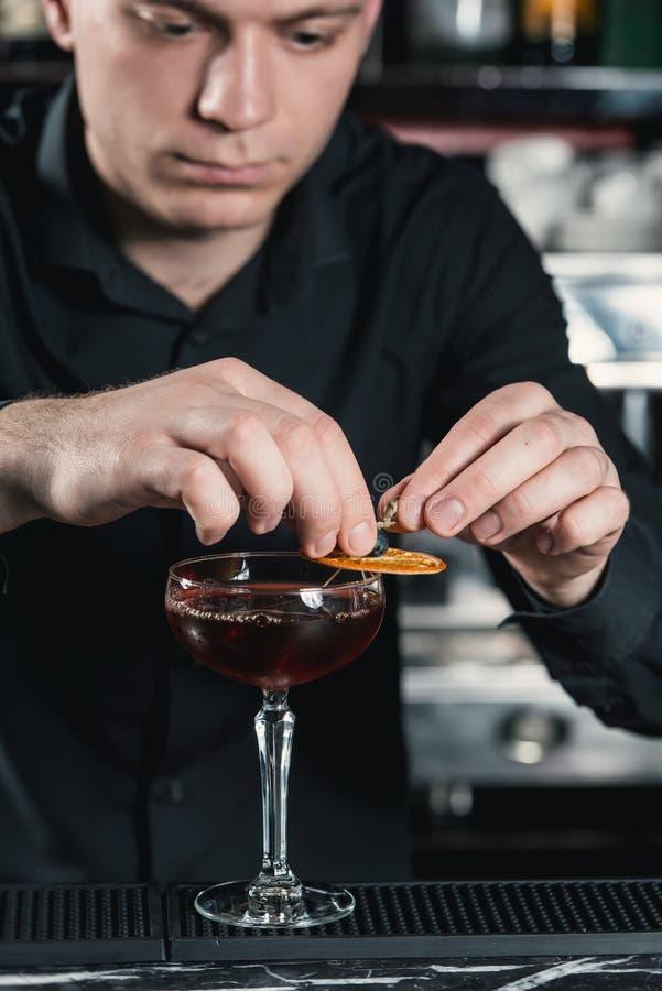 Barman que faz o cocktail do revestimento do cocktail de Boulevardier que põe a fatia alaranjada sobre a parte superior Barra em  fotos de stock royalty free