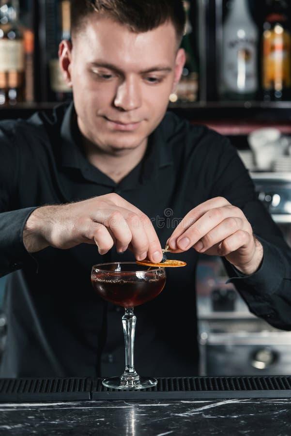 Barman que faz o cocktail do revestimento do cocktail de Boulevardier que põe a fatia alaranjada sobre a parte superior Barra em  foto de stock royalty free