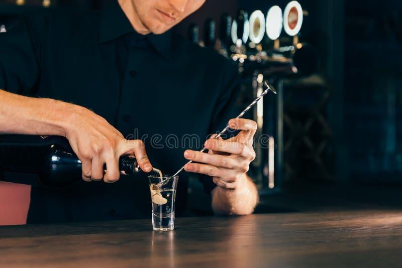 Barman que faz o coctail do álcool no restaurante O empregado de bar perito está adicionando o cocktail do ingrediente no clube n imagens de stock