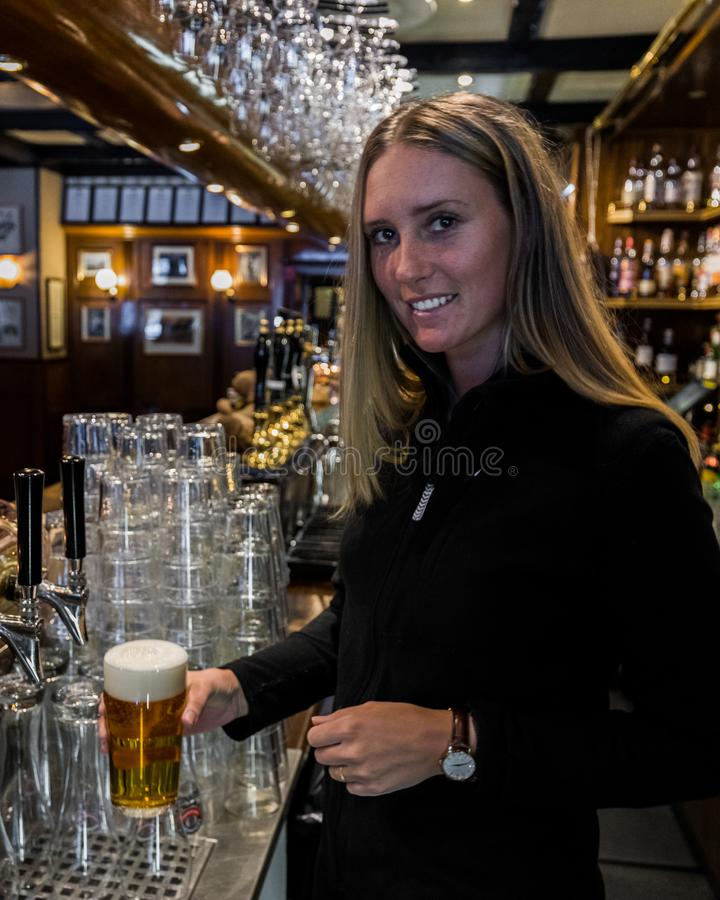 barman que guarda o vidro de cerveja foto de stock