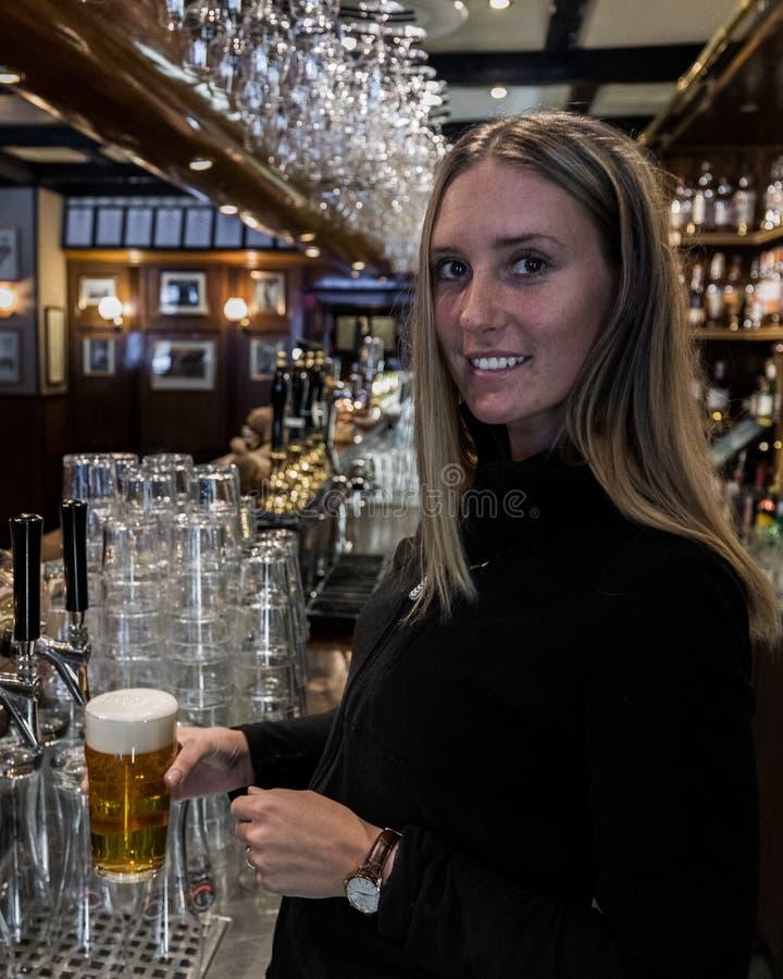 barman que guarda o vidro de cerveja imagem de stock