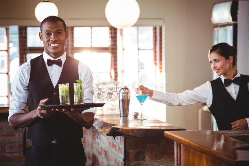 Barman que guarda uma bandeja do serviço com dois vidros de cocktail imagem de stock royalty free
