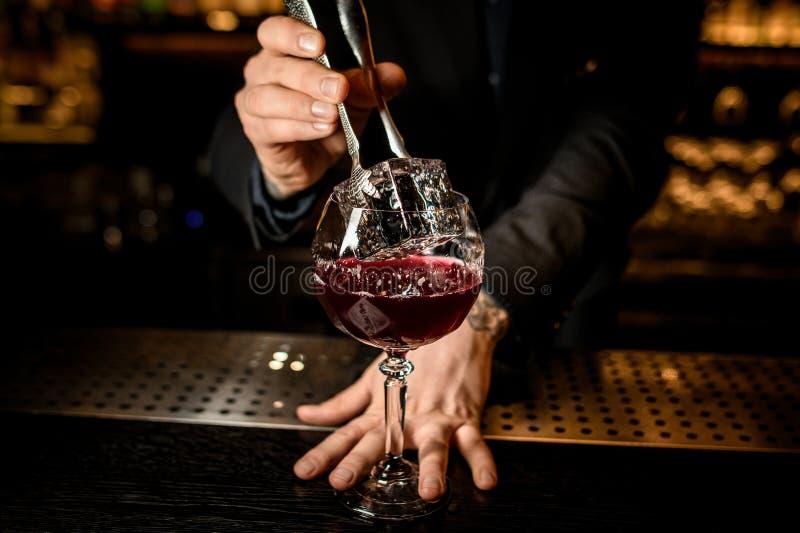 Barman que põe o cubo de gelo em um cocktail com fórceps fotografia de stock royalty free
