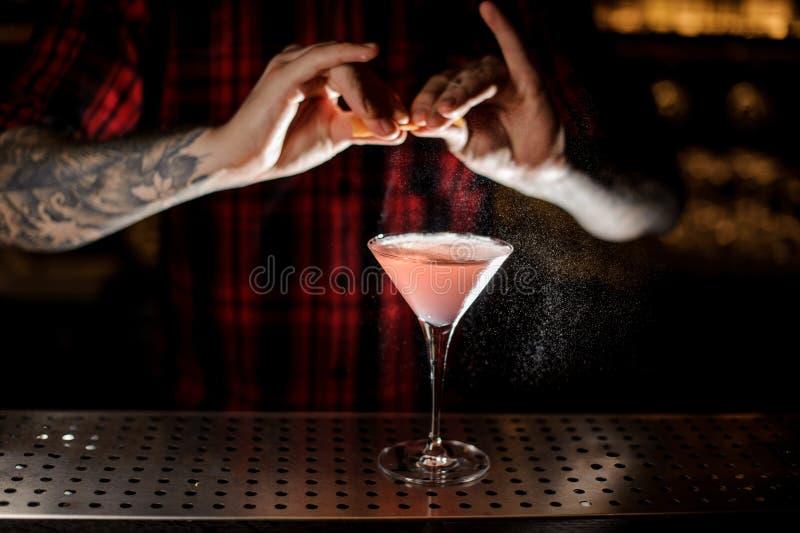 Barman que polvilha o suco da casca alaranjada em um cockt cosmopolita imagens de stock