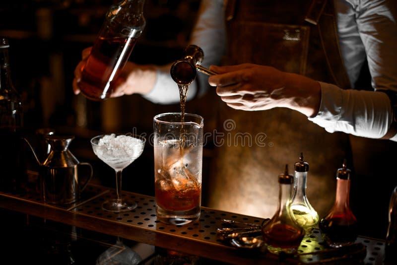 Barman que prepara o cocktail do álcool usando o jigger com punho fotos de stock