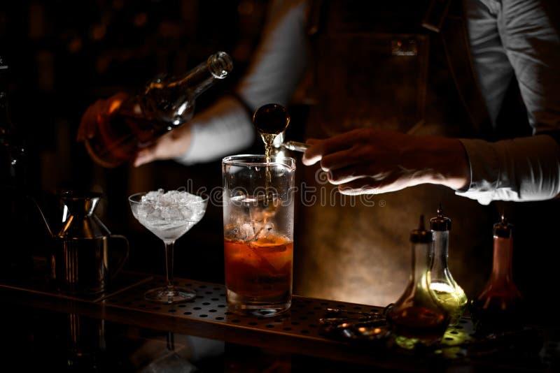 Barman que prepara um cocktail do álcool usando o jigger fotografia de stock