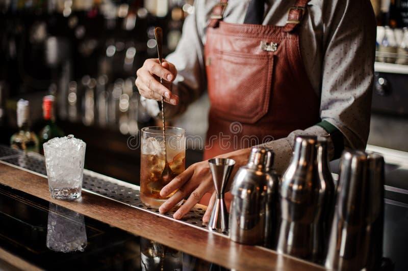 Barman que refrigera para fora o gelo de mistura do vidro de cocktail com uma colher fotografia de stock royalty free