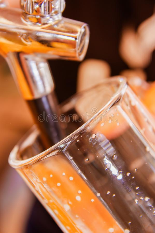 Barman ręka przy piwa klepnięciem nalewa łyknięcia lager piwa porcję w pubie w zamazanym tle lub restauraci, fotografia royalty free