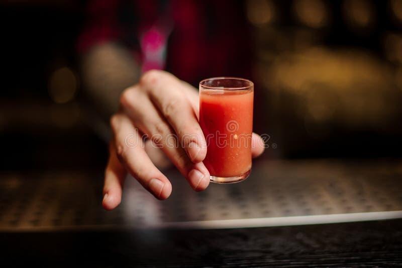 Barman ręka trzyma szkło strzelał silny pomidorowy alkoholiczny napój fotografia stock