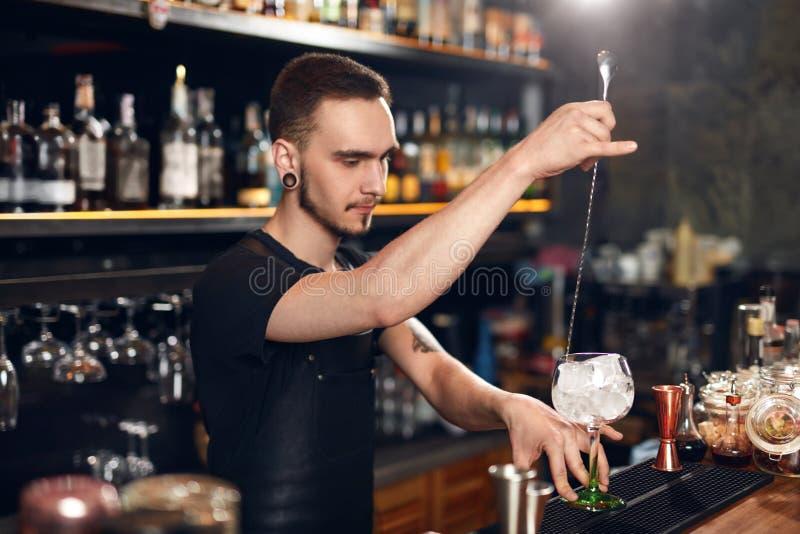 Barman robi koktajlowi Barmanu kładzenia lód W szkle obrazy royalty free