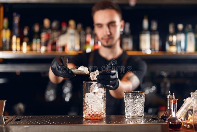 Barman robi koktajlowi Barmanu kładzenia lód W szkle obraz stock