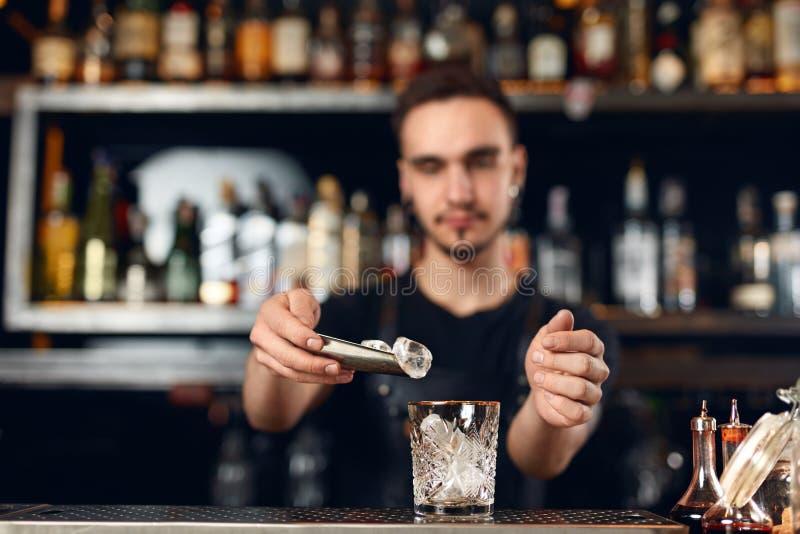 Barman robi koktajlowi Barmanu kładzenia lód W szkle zdjęcia royalty free