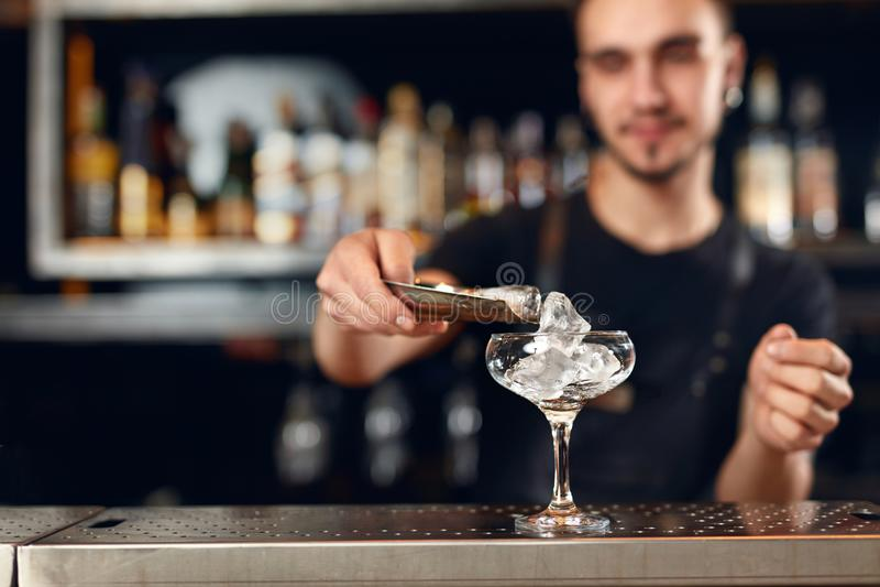 Barman robi koktajlowi Barmanu kładzenia lód W szkle zdjęcie stock