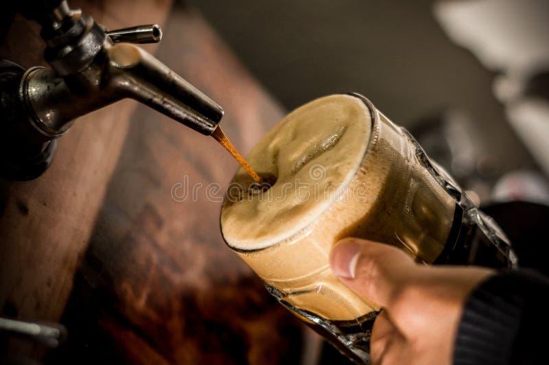 Barman se remplissant de la bière blonde de métier dans un verre de pinte photographie stock