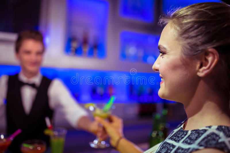 Barman serving cocktail to woman. Barman serving cocktail to women at nightclub royalty free stock photo